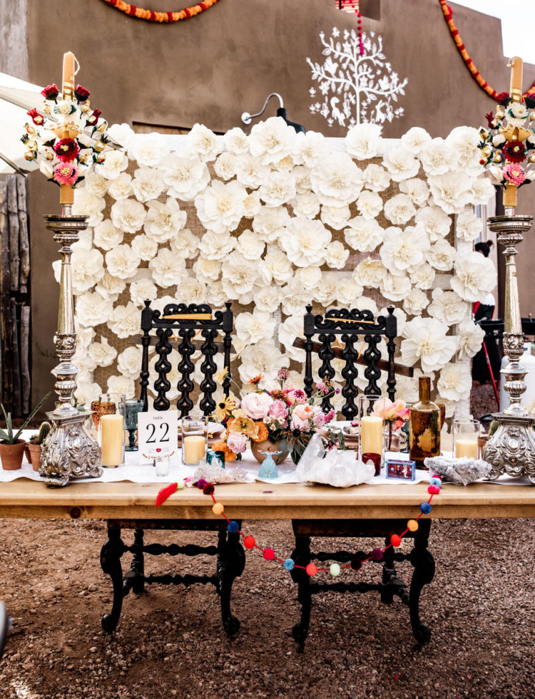 The sweetheart table features a white fabric bloom backdrop