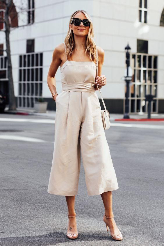 an off white jumpsuit with spaghetti straps, wideleg pants, nude shoes and a neutral bag for summer