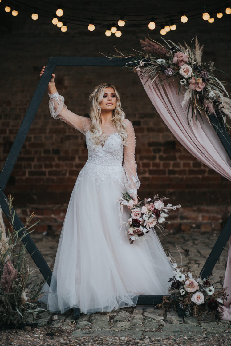A black hex wedding arch was decorated with blush and mauve blooms, pampas grass and greenery