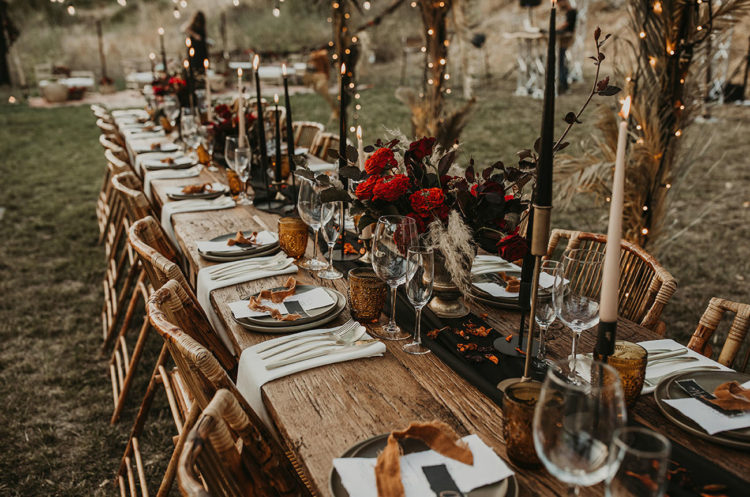 The wedding table was set with bright blooms, black candles, dried elements