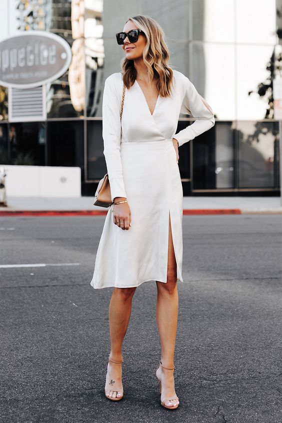 a casual knee white dress with a V neckline, long sleeves, a front slit, nude shoes and a camel bag