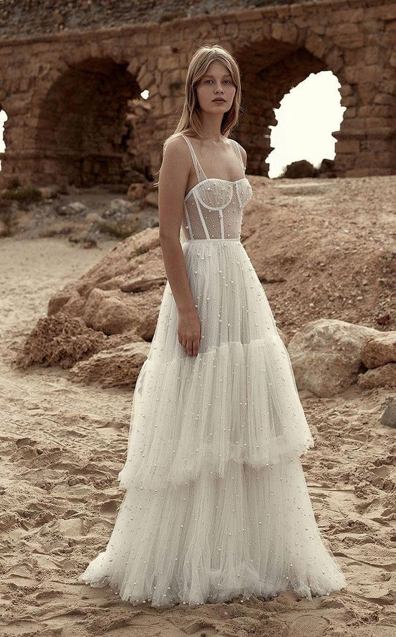 a gorgeous wedding dress, fully embellished with pearls, with a bustier bodice and a layered tulle skirt