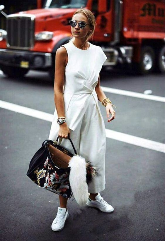 a casual white jumpsuit with one cap sleeve, a high neckline, drapery, wideleg pants, white sneakers