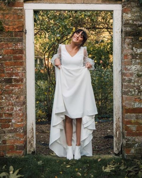 white leather booties paired with a modern plain wedding dress with sheer sleeves for a trendy look