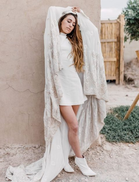 white leather booties, a white plain mini dress and a lace capelet with a train for a trendy modern look with a touch of boho