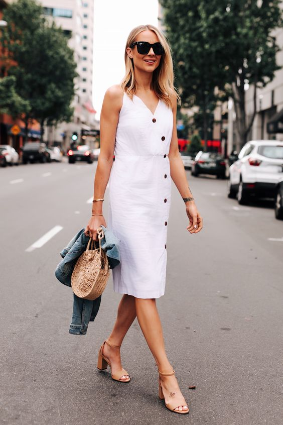 a casual white knee summer dress with no sleeves, a V neckline, black buttons, nudde shoes, a wicker bag and a denim jacket