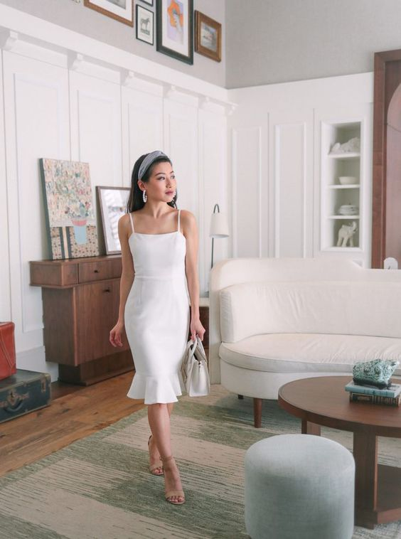 a cute white sheath knee dress with spaghetti straps, nude shoes and a white bag for a summer bride