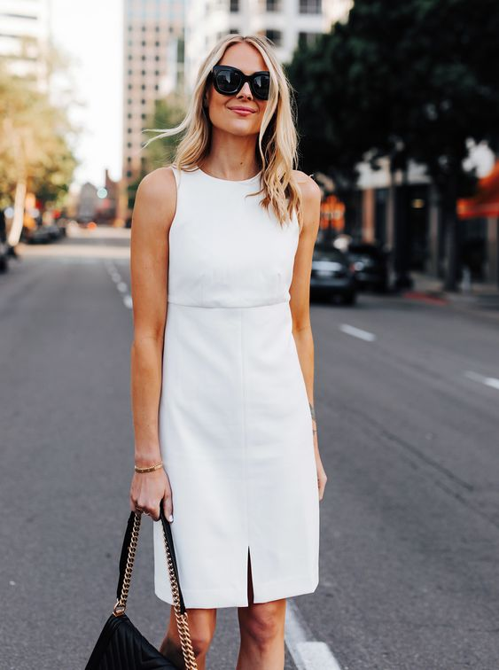a little white knee dress with a high neckline, no sleeves, a front slit for a spring or summer bride-to-be