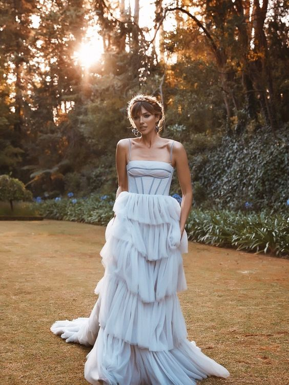 a creative light blue wedding dress inspired by antique ones, with a corset bodice on spaghetti straps and a tiered tulle skirt