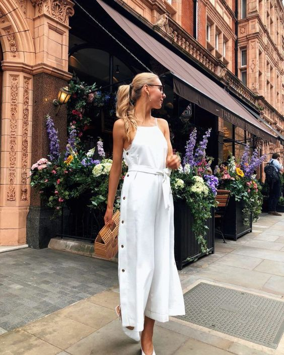 a white midi dress with buttons on one side,  halter neckline, white shoes and a wooden bag for a summer bride-to-be