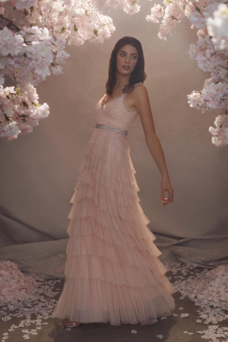 a romantic pink wedding dress with ruffle straps and a necklace, a tiered tulle skirt and an embellished sash