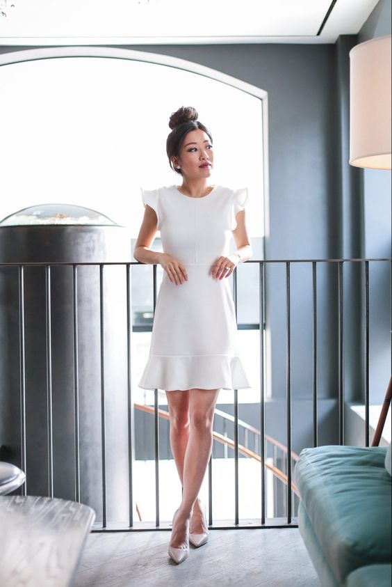 a white mini dress with cap ruffle sleeves, a high neckline and nude shoes for a casual or minimalist bride-to-be