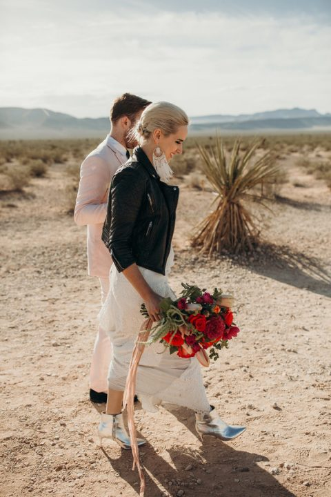 a lace wedding dress, silver boots, a black leather jacket and statement boho earrings for an ultimate bridal look