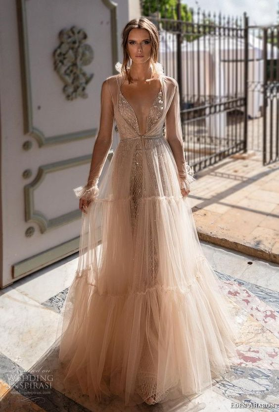 a tan embellished wedding dress with a plunging neckline, a tiered tulle skirt and a sheer overdress