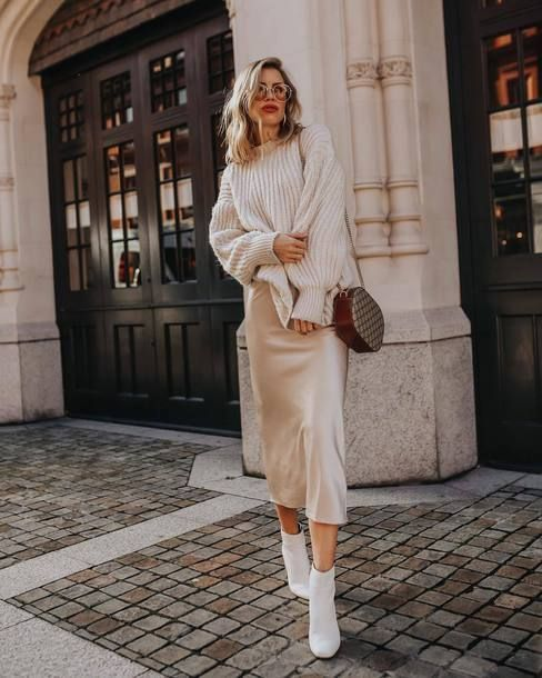 a winter outfit with an oversized sweater, a silk slip midi skirt, white booties and a brown crossbody bag