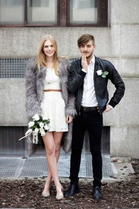 a lace mini dress with a brown belt, grey shoes and a grey faux fur coat for a modern bride