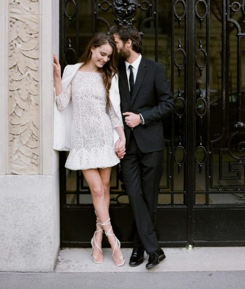 a romantic mini lace wedding dress with long sleeves, a high neckline, an open back and plain capelet