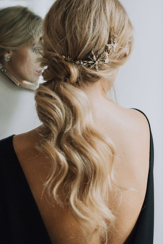 a low wavy ponytail with a messy top accented with a cool shiny star headcomb is a gorgeous idea