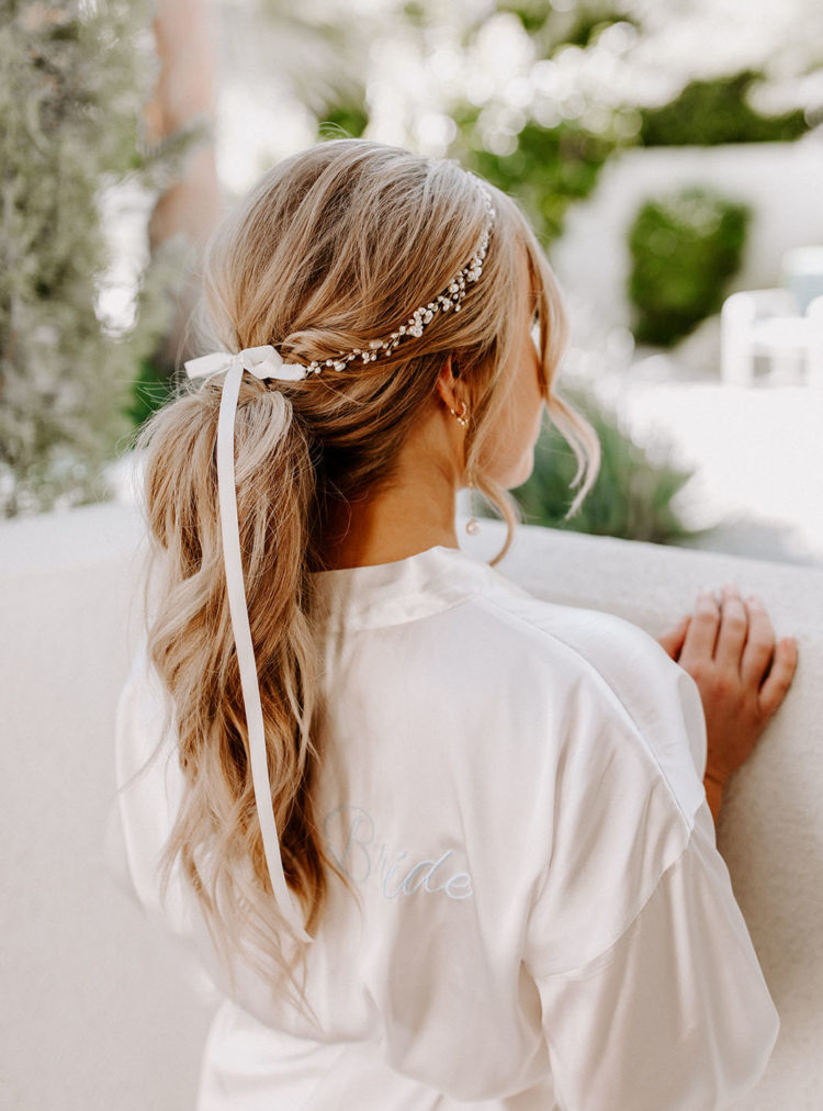 The bride was rocking a cute wavy low ponytail accented with a pearl hair vine