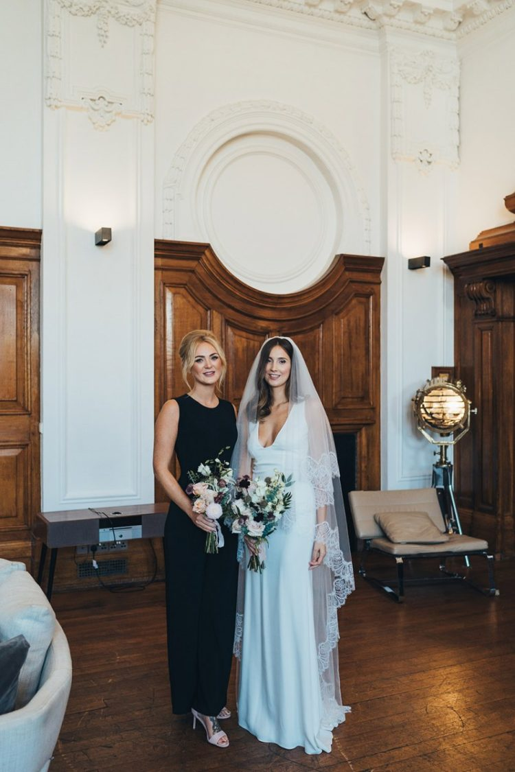 The bride was wearing a minimalist sleeveless plunging neckline wedding dress with a train and a cathedral veil