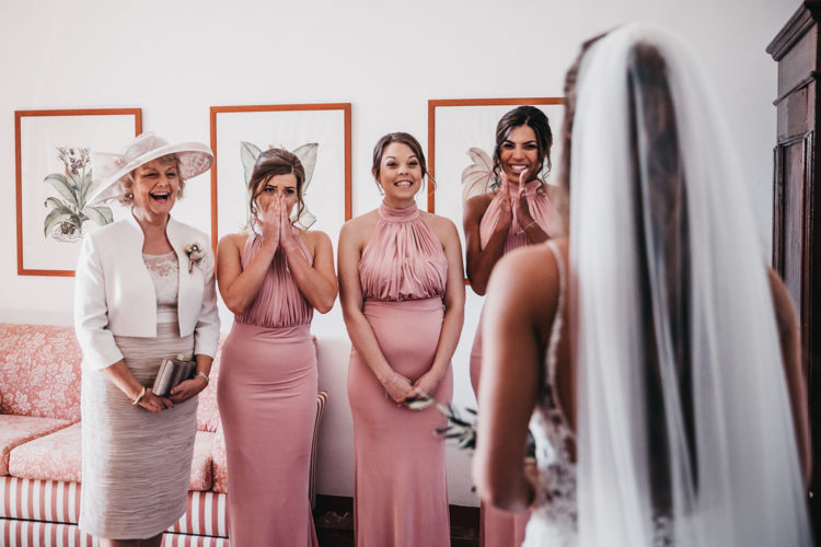 The bridesmaids were rocking matching halter neckline pink maxi dress with draped bodices