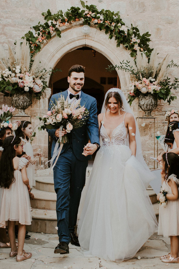 The groom was wearing a blue suit with a black bow tie, and the bride was wearing a wedding gown with a lace bodice and a deep plunging neckline