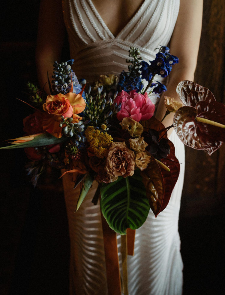 The wedding bouquet was done colorful, with bright blooms and large tropical leaves