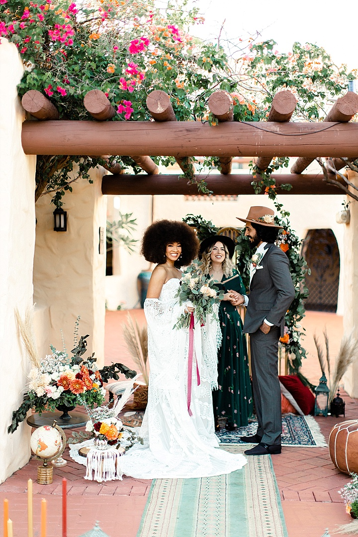 The bride was rocking a boho lace strapless wedding dress with a train and bell sleeves