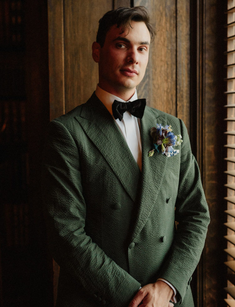 The groom was rocking a creative green suit, a dark velvet bow tie and a bold boutonniere