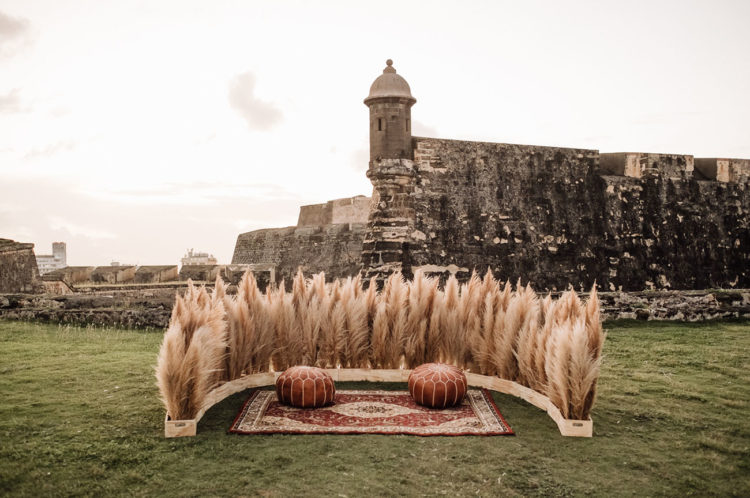 The wedding ceremony space was done with pampas grass, boho rugs and leather ottomans