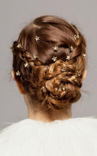a fully braided low updo with tiny gold rhinestone star pins for a celestial look