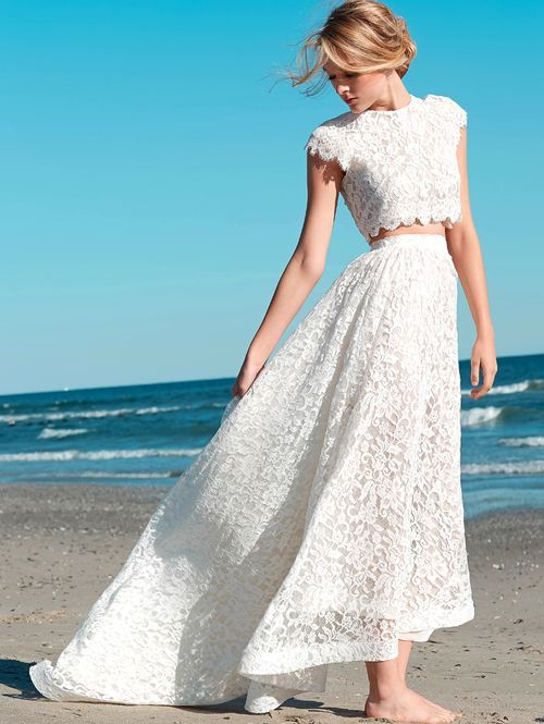 a two piece lace wedding dress with a cap sleeve crop top and an A-line high low skirt to show off some skin