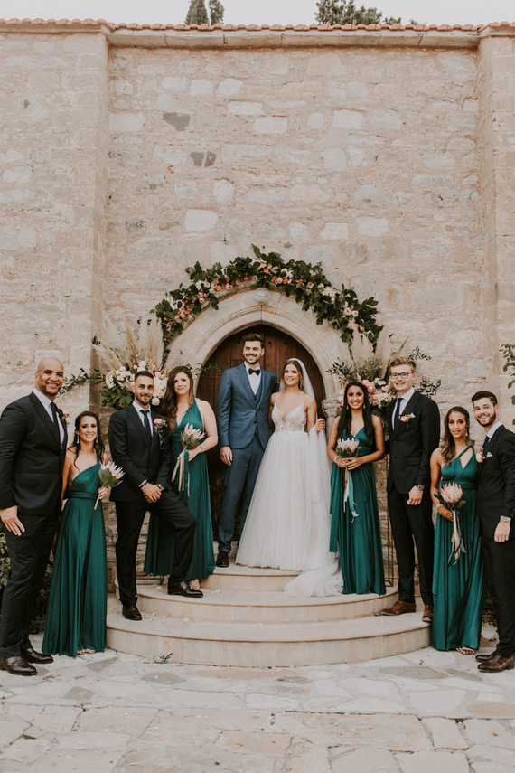 The groosmen were wearing black suits and ties, and the bridesmaids were rocking gorgeous emerald maxi dresses