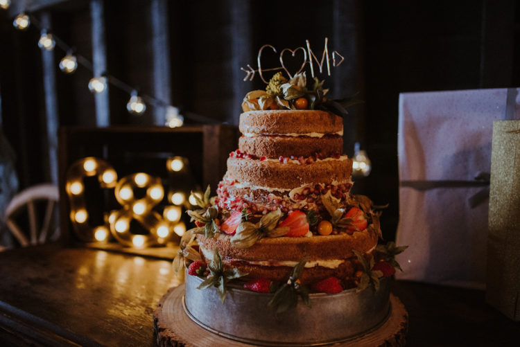 The wedding cake was a naked one decorated with fresh fruits and blooms
