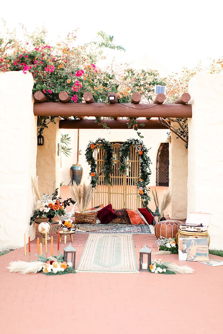 The wedding ceremony space was done with boho rugs, lots of greenery, pampas grass and blooms, candle lanterns and bright pillows