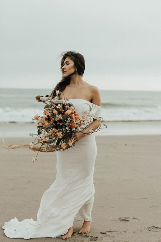 a simple and very flowy off the shoulder wedding dress with a train is a nice flowing wedding dress for a beach wedding
