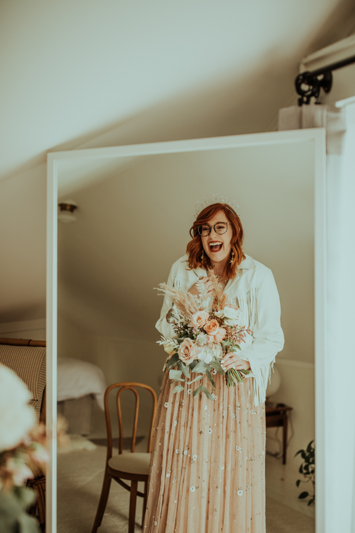She was carrying a soft blush and neutral wedding bouquet and covered with a white fringe jacket
