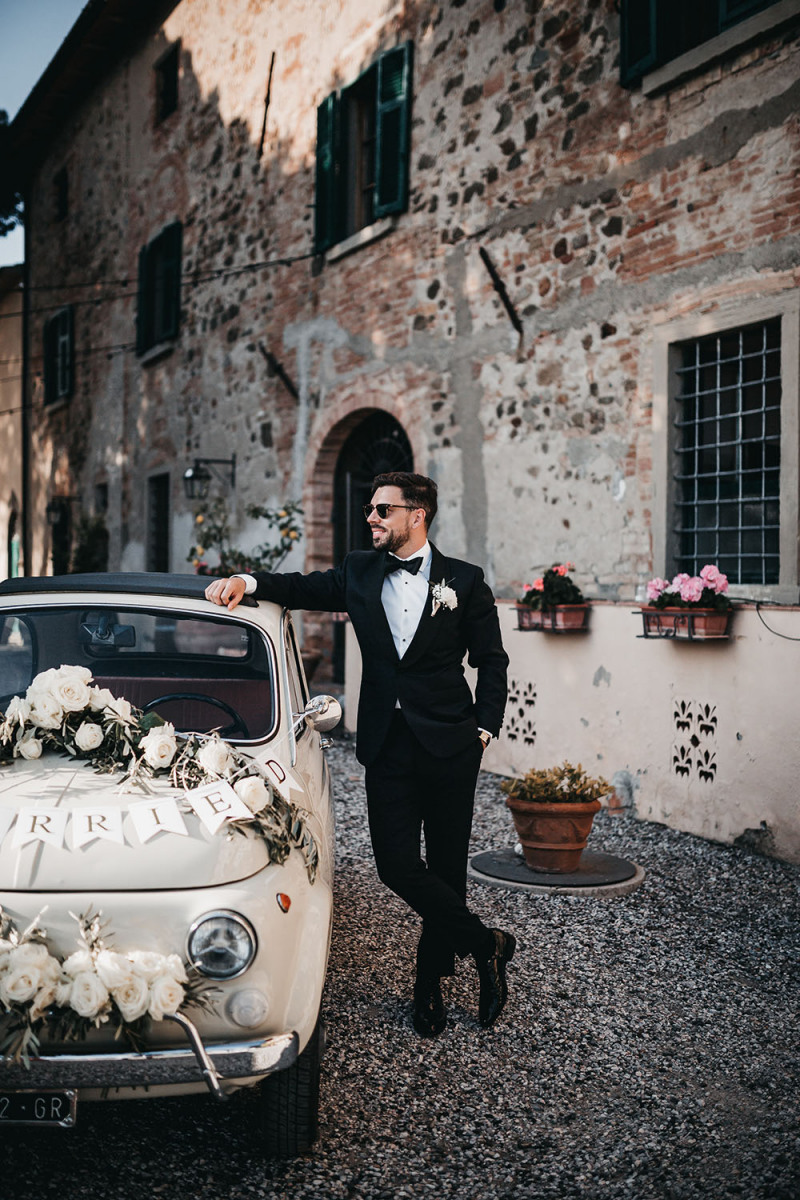 The couple decorated an old Fiat with blooms for their weddign escape