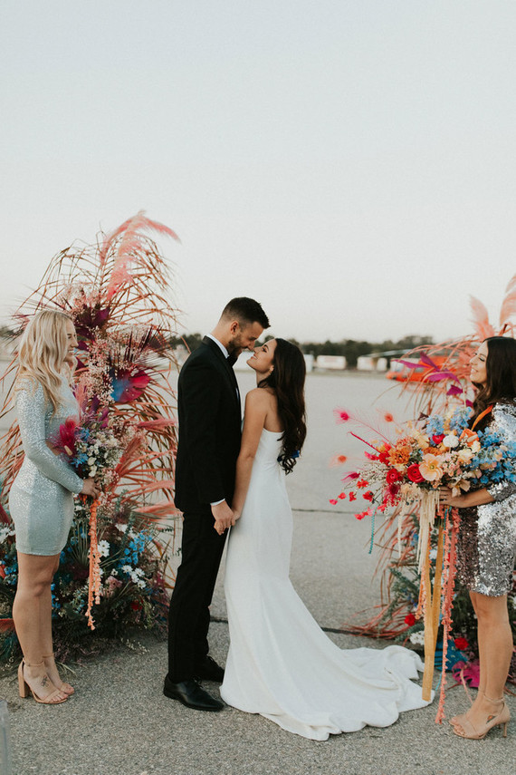 The wedding altar was done super bright and colorful, with fronds and pampas grass
