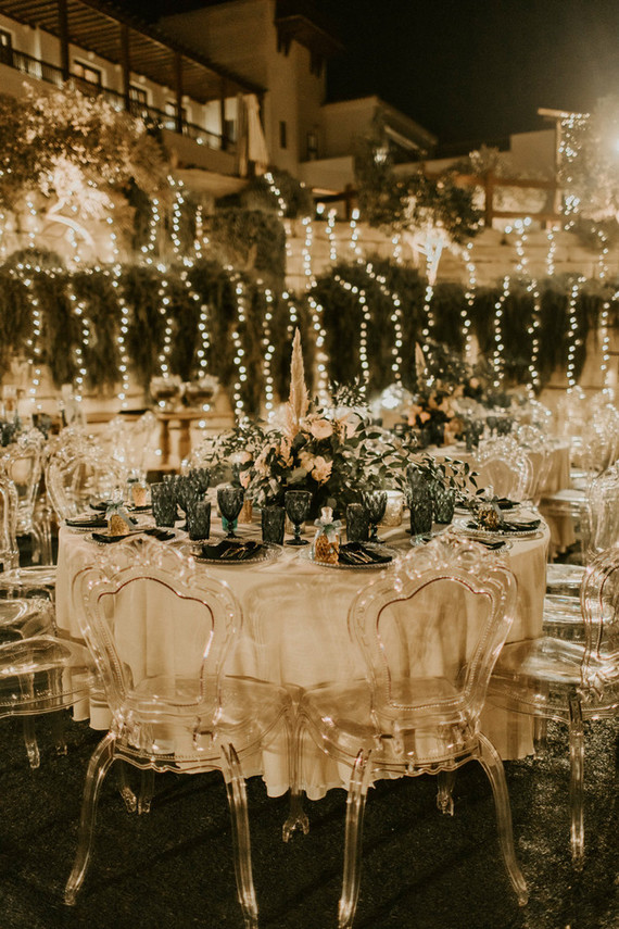 The wedding reception was outdoors, with neutral blooms and greenery and cool ghost chairs