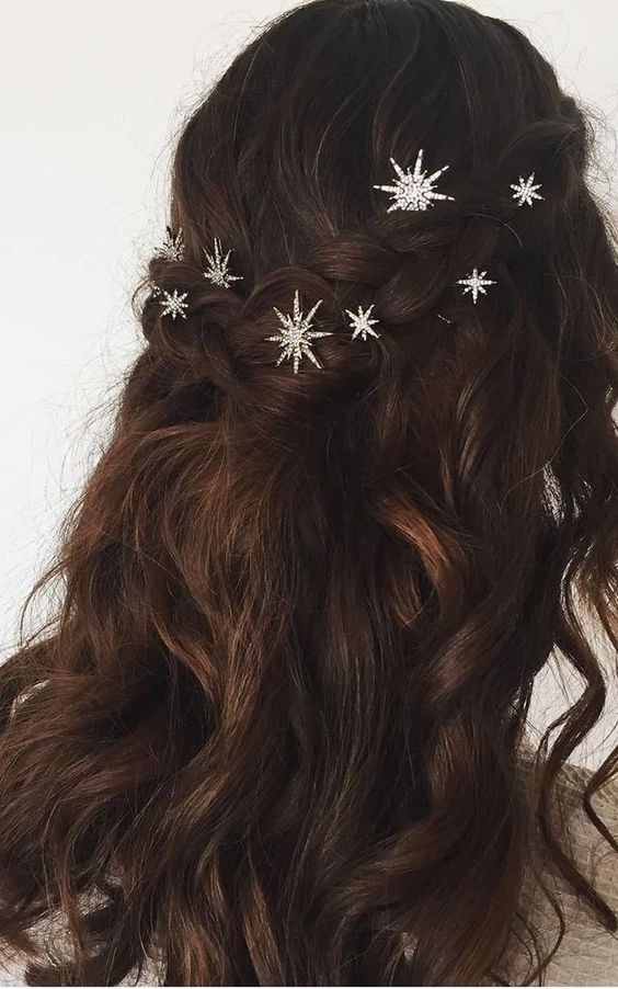 a dark wavy half updo with a braided halo and some shiny star pins is a beautiful idea for a celestial bride