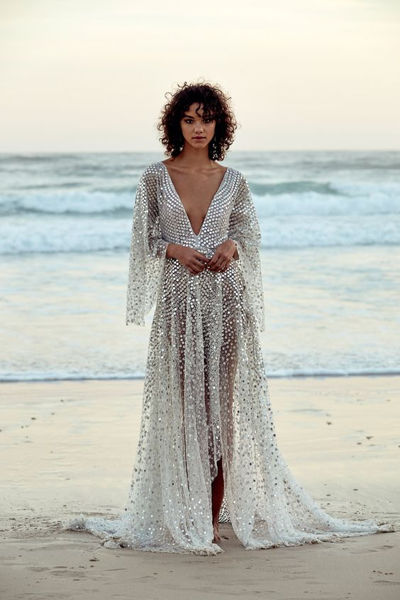 a sparkling silver A-line dress with a plunging neckline and bell sleeves plus a high low skirt lets the skin breathe