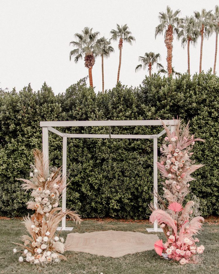 The wedding arch was done with pink fronds, pampas grass and blush blooms
