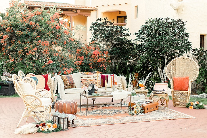 The wedding lounge was done with rattan furniture, boho rugs, suitcases, ottomans, candles and vintage cameras