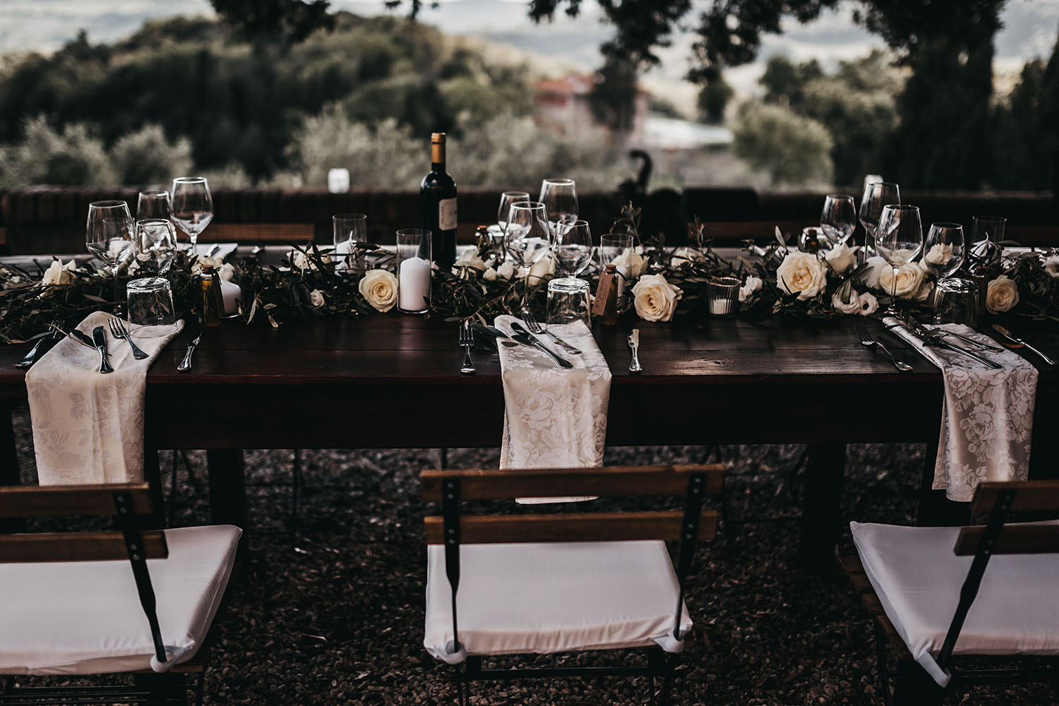 The table decor was done with white blooms, greenery and candles and the textiles were printed