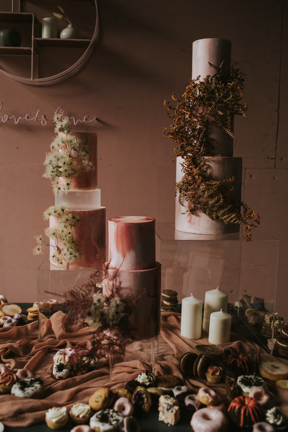 The wedding cakes were pink, with dried blooms and leaves