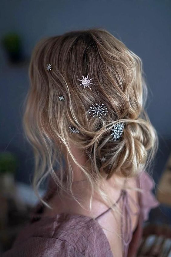 a messy and wavy low updo with various crystal star hair pins looks chic and very celestial