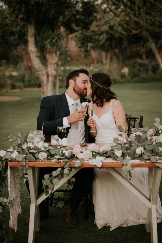 organize a cool backyard sweetheart table with beautiful decor, candles, blooms and delicious food