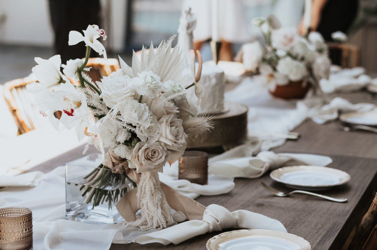 The decor was simple and white, with the wedding bouquet of white fronds and pale blooms
