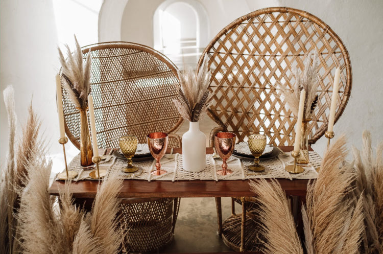 The table was styled with a macrame runner, bright glasses, feathers and pampas grass